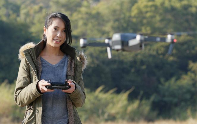 Une télépilote de loisirs contrôlant un drone grand public (photo Adobe Stock)