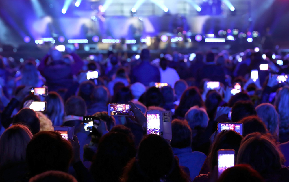 De plus en plus de spectateurs sortent leur smartphone pendant un spectacle.  (photo Adobe Stock)