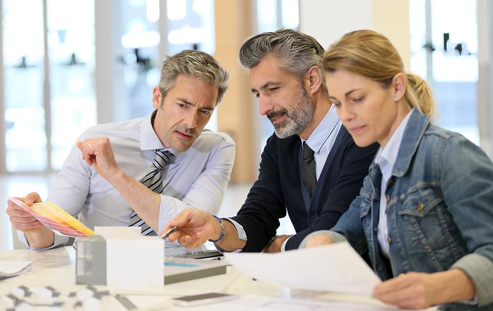 Une équipe d'architectes travaillant sur la maquette d'un bâtiment (photo Adobe Stock)