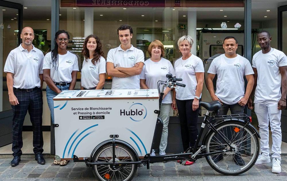 L'équipe d'Hublo posant l'un des triporteurs électriques qui permet de collecter le linge (photo Hublo)